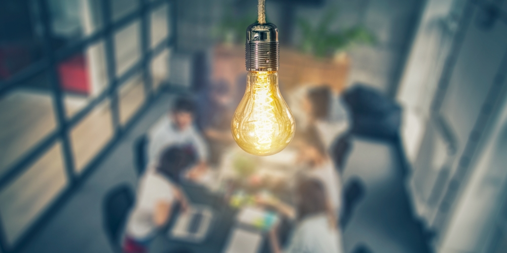 lit lightbulb above desk surrounded by employees